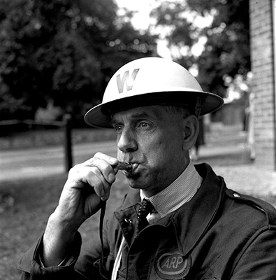 World War II. 1940. An Air Raid Warden blows his whistle during a practice drill.
